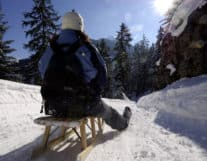 Guy sledding enjoying winter activities near Interlaken