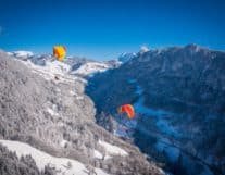 Two paragliders in the air over Swiss Alps