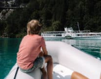 Kid enjoying lake activity in a motor boat in interlaken